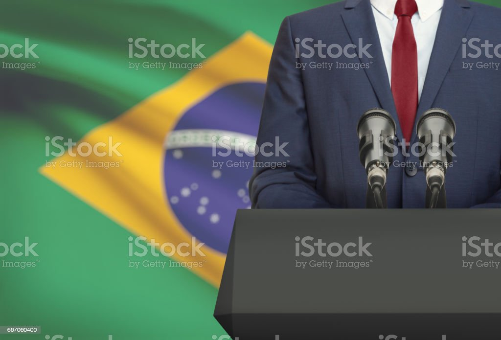 Businessman or politician making speech from behind a pulpit with national flag on background - Brazil - foto de acervo