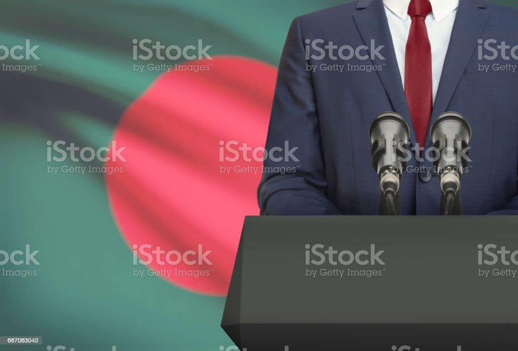 Businessman or politician making speech from behind a pulpit with national flag on background - Bangladesh - foto de stock