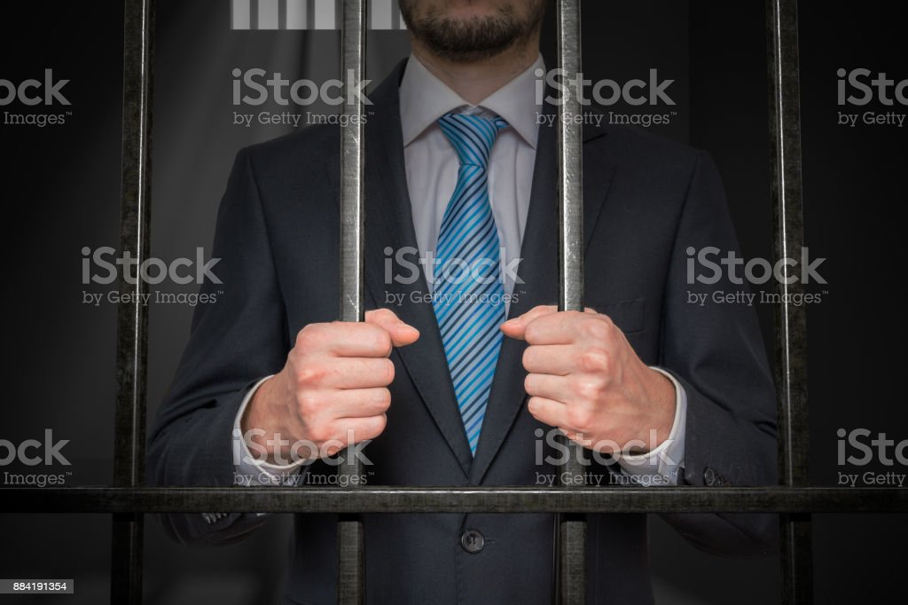 Businessman or politician with handcuffs behind bars in prison cell. stock photo