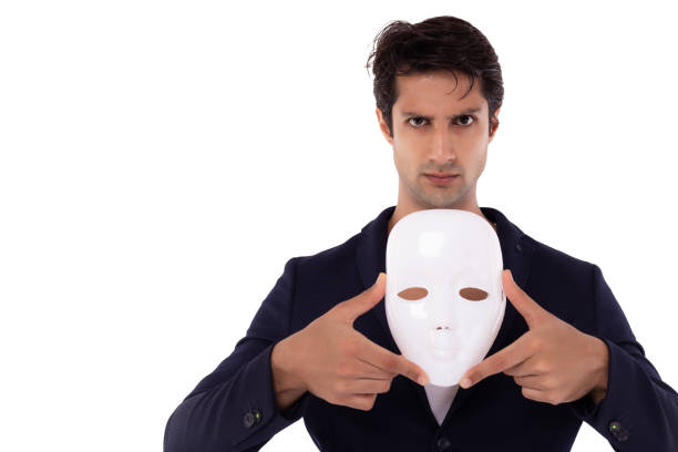 Businessman or white collar worker crime hold white mask. dishonest cheating person. Faking and betray business partnership, dishonest hiding in mask. Cheating person showing mask, two faced person stock photo