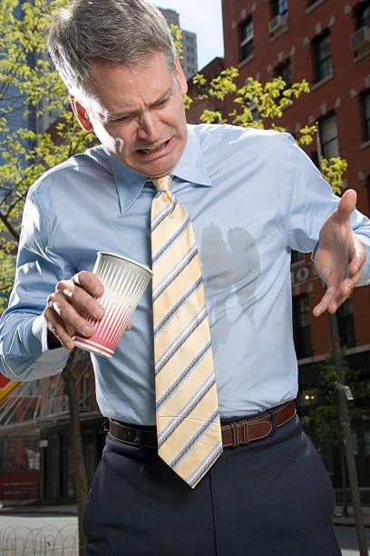Businessman outdoors, coffee spilt on shirt stock photo