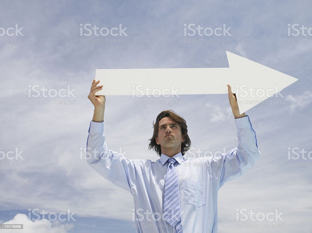 Businessman outdoors holding blank arrow with sky in background stock photo