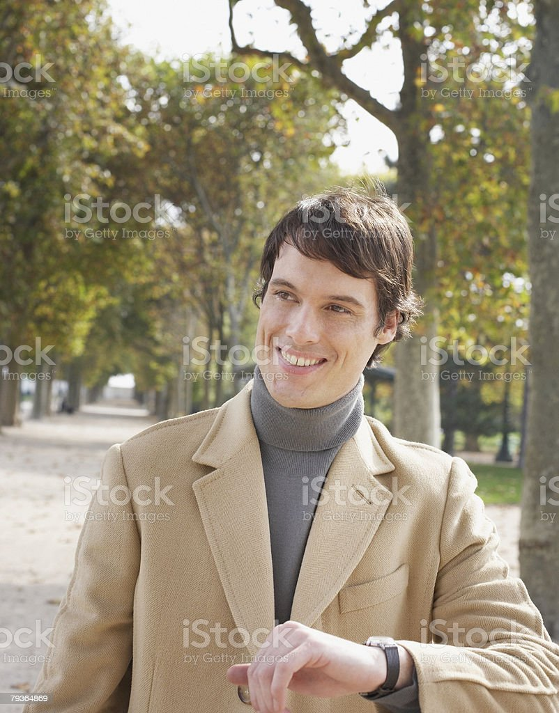 Businessman outdoors in park checking the time royalty-free stock photo