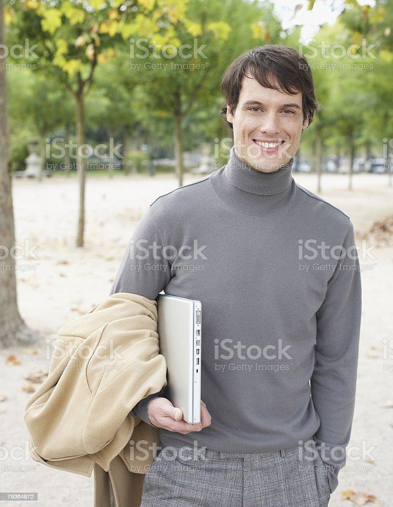 Geschäftsmann hält laptop im Freien im park Lizenzfreies stock-foto