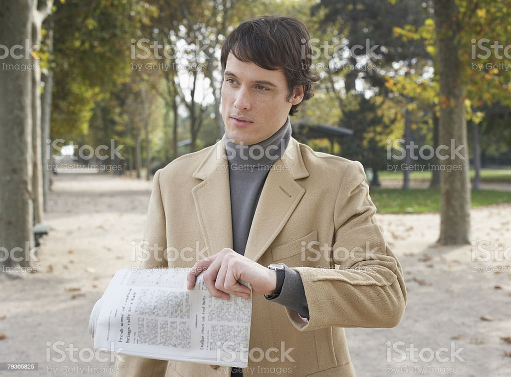 Businessman outdoors in park holding newspaper royalty-free stock photo