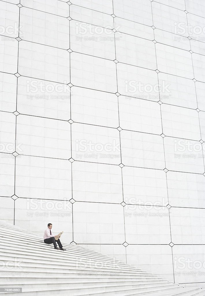 Businessman outdoors on staircase reading newspaper stock photo