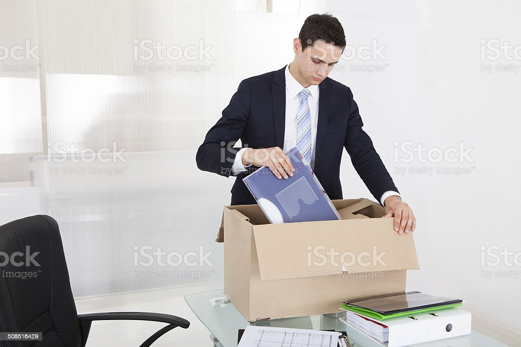 Businessman Packing Files In Cardboard Box In Office stock photo