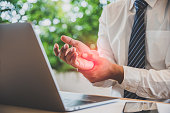 istock Businessman pain in hands while woking with laptop. Office syndrome concept. 1124980882