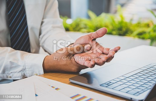 Businessman pain in hands while woking with laptop. Office syndrome concept.
