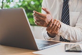 istock Businessman pain in hands while woking with laptop. Office syndrome concept. 1153454323