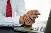 istock Businessman pain in hands while woking with laptop. 1209221337