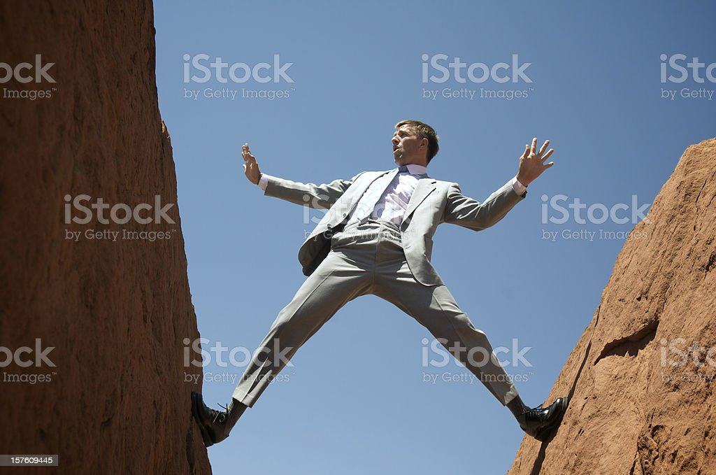 Businessman Panics as He Balances between Rocks stock photo