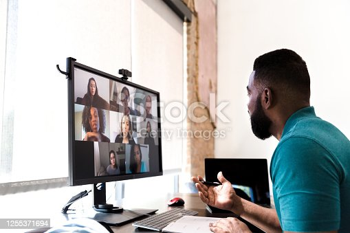 A mid adult man gestures while talking with a group of colleagues during a virtual staff meeting via video conference.