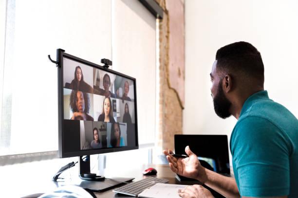 Businessman participates in virtual staff meeting stock photo