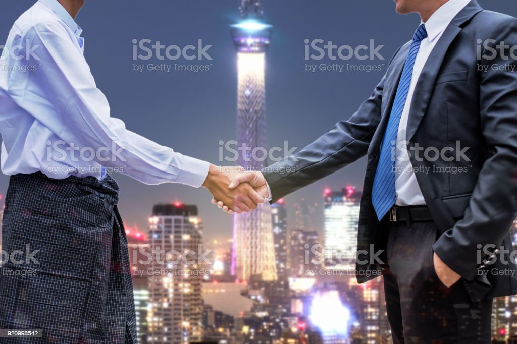 Businessman partnership handshake of asean economic community on the city stock photo