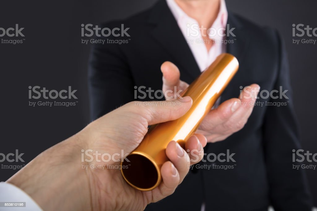 Businessman Passing A Golden Relay Baton stock photo