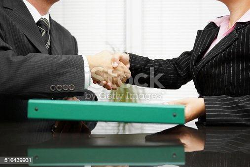 istock businessman passing binder with documentation  to his client while handshaking 516439931