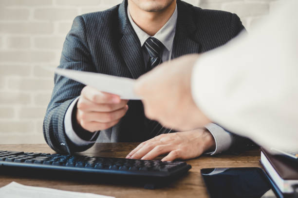 Businessman passing document to manager in the office stock photo
