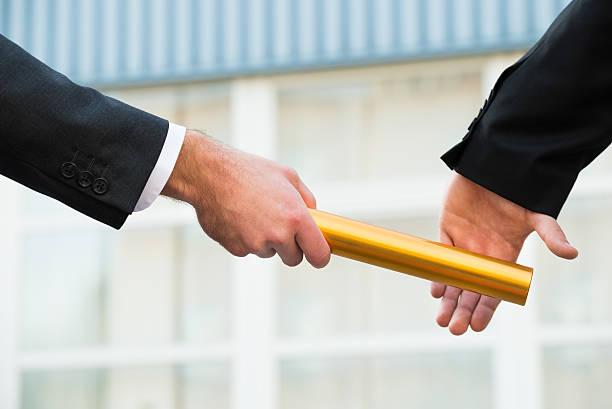 businessman passing relay baton to colleague - staffelstab stock-fotos und bilder