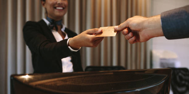 businessman paying for hotel room at reception - airport check in counter stock pictures, royalty-free photos & images