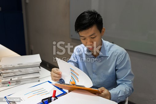 926239360 istock photo Businessman paying high attention to reviewing sale report 495660698