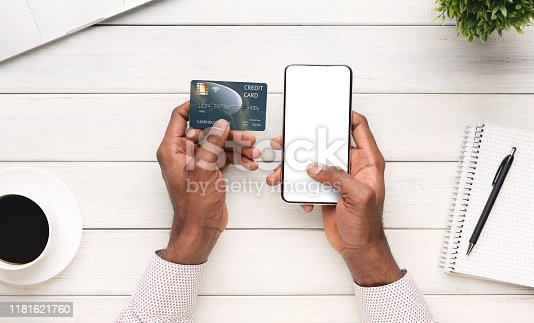 1173546354 istock photo Businessman paying his bills online using smartphone with blank screen 1181621760