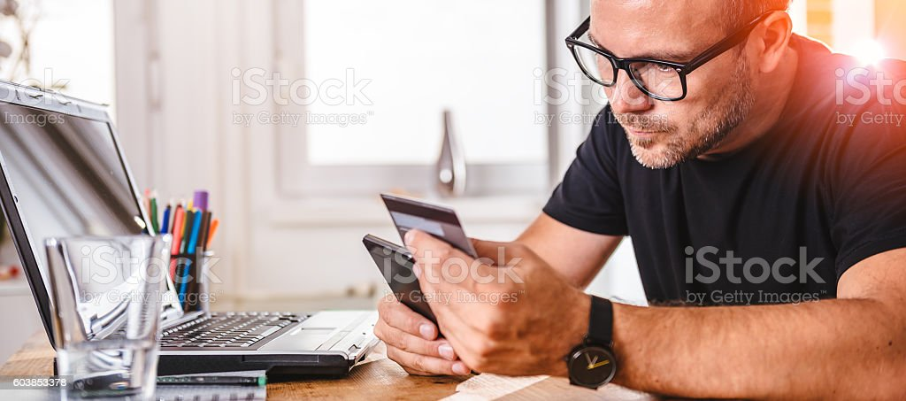 Businessman paying with credit card on smart phone stock photo