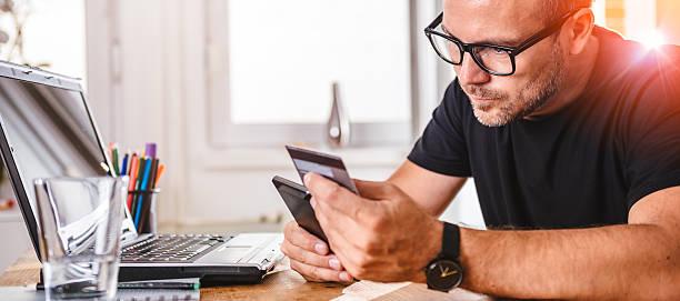 businessman paying with credit card on smart phone - brille bestellen stock-fotos und bilder