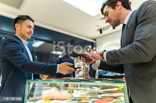 istock Businessman paying with smart phone in shopping mall 1161197400