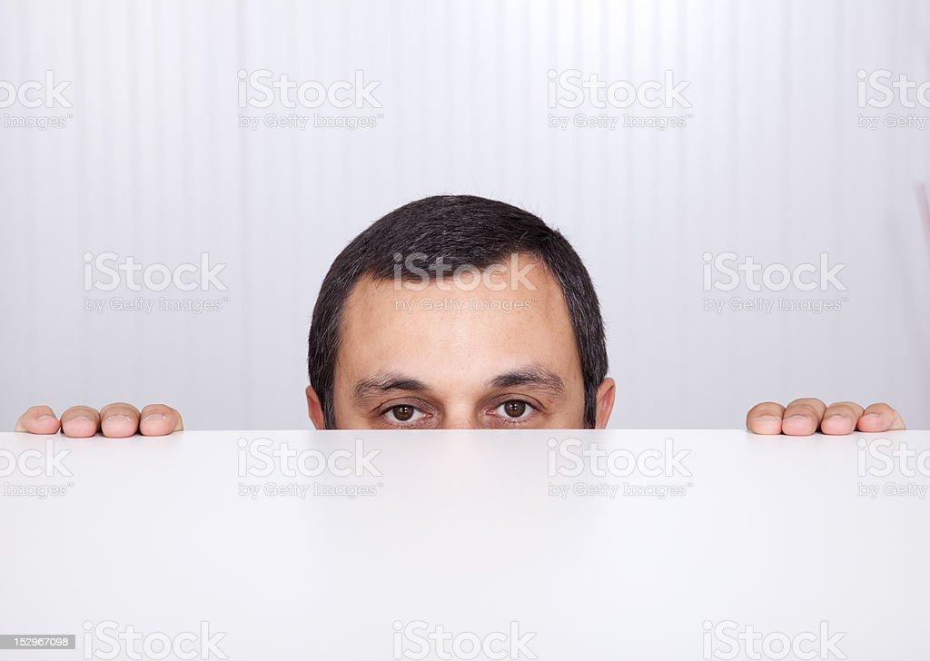 Businessman peeking behind the desk stock photo