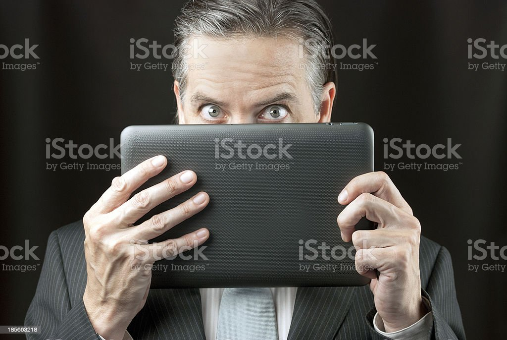 Businessman Peeks Over His Tablet royalty-free stock photo
