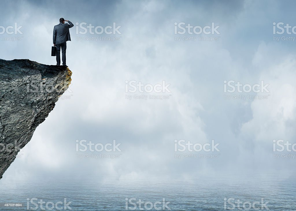 Businessman Peering Out To Sea stock photo