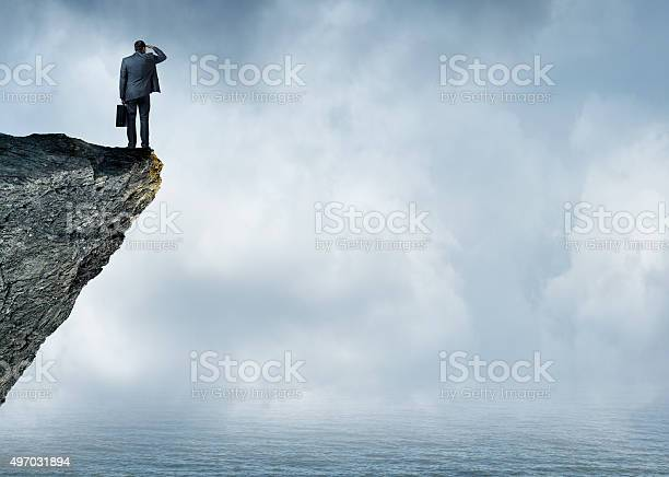 Photo of Businessman Peering Out To Sea