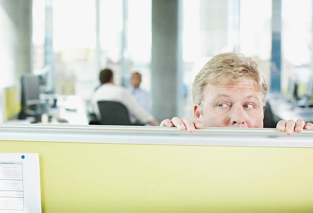 businessman peering over cubicle wall - achterdocht stockfoto's en -beelden