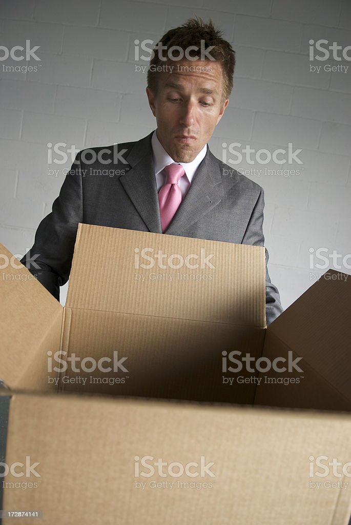 Curious businessman peers into an open cardboard box