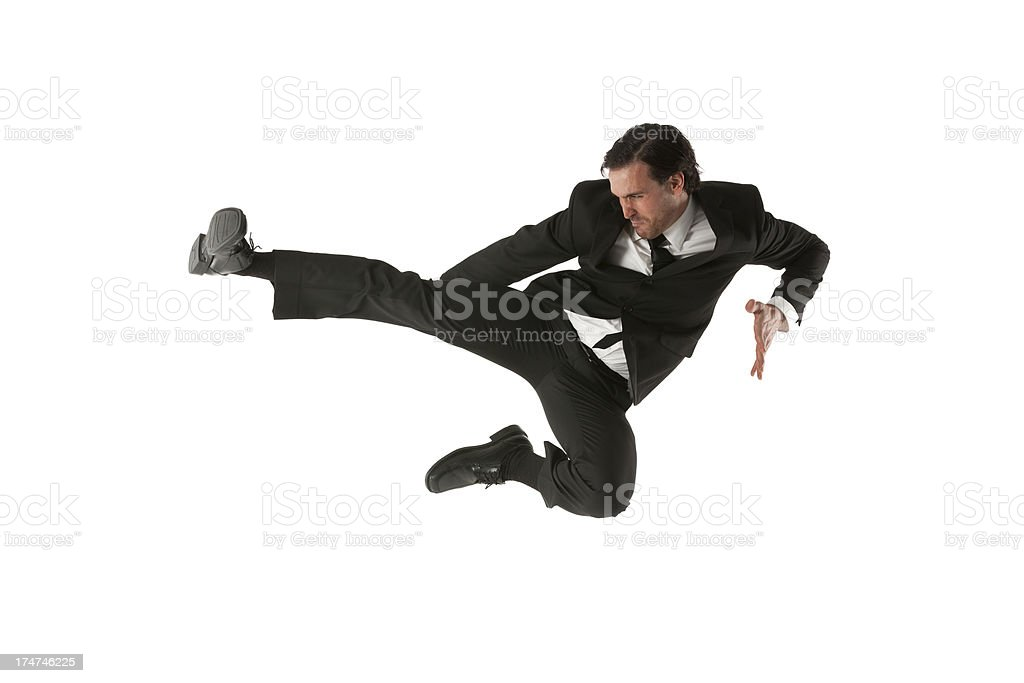 Businessman performing a flying kick stock photo