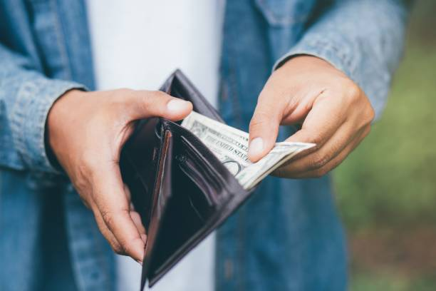 businessman person holding an wallet in the hands of an man take money out of pocket. - wallet stock pictures, royalty-free photos & images