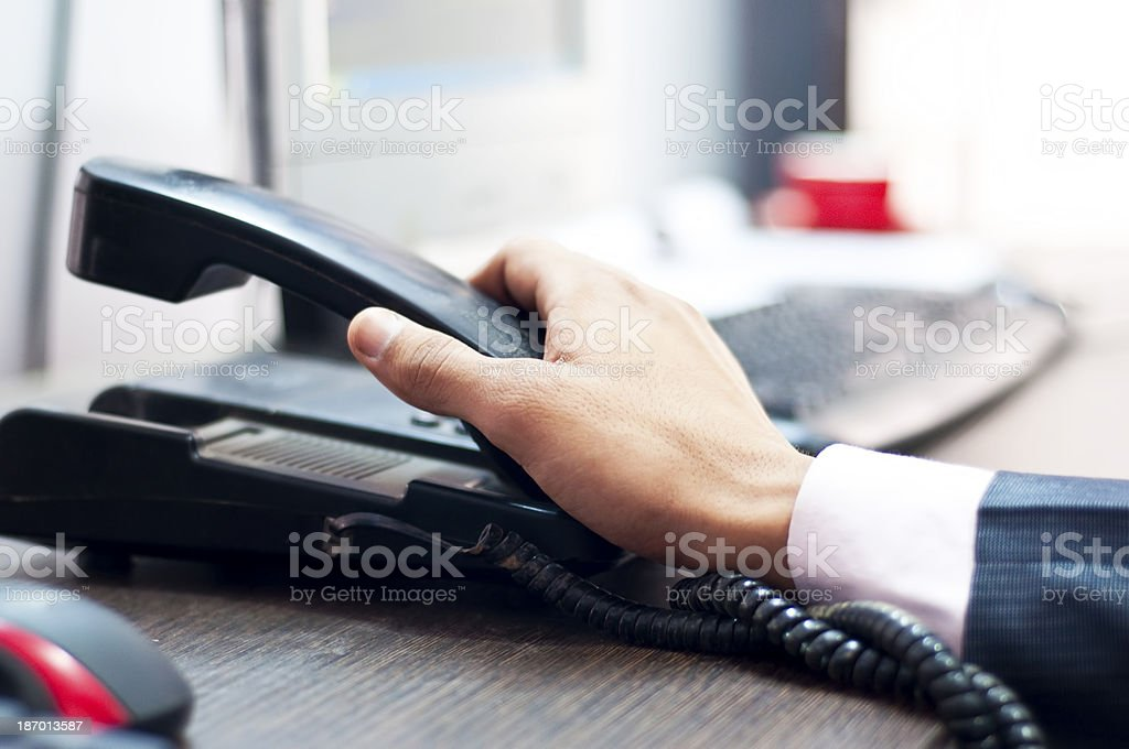 Businessman picking up a phone stock photo
