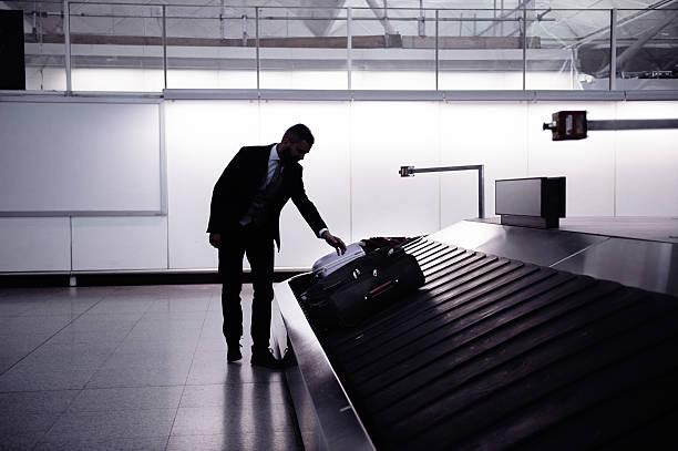 businessman picking up suitcase on luggage conveyor belt, airpor - airport pickup stockfoto's en -beelden
