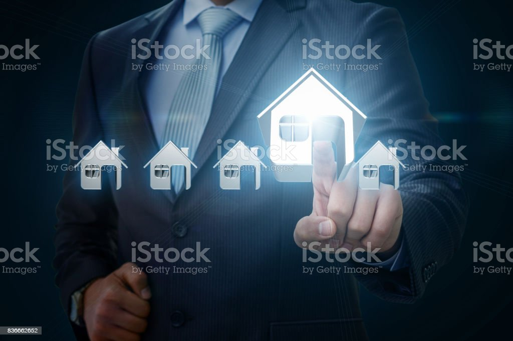 Businessman picks a house . stock photo