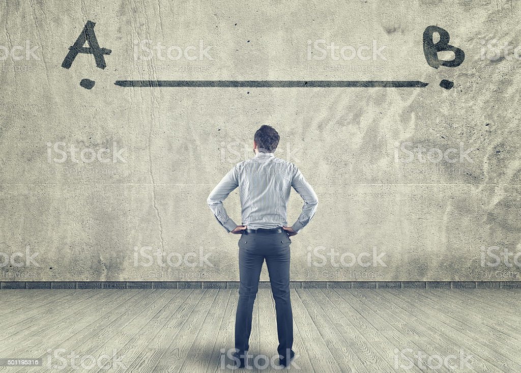 Businessman looking at a line between a to b painted on a wall