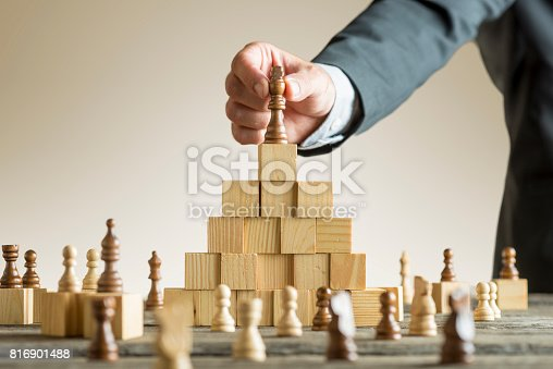 istock Businessman placing a chess piece on blocks 816901488