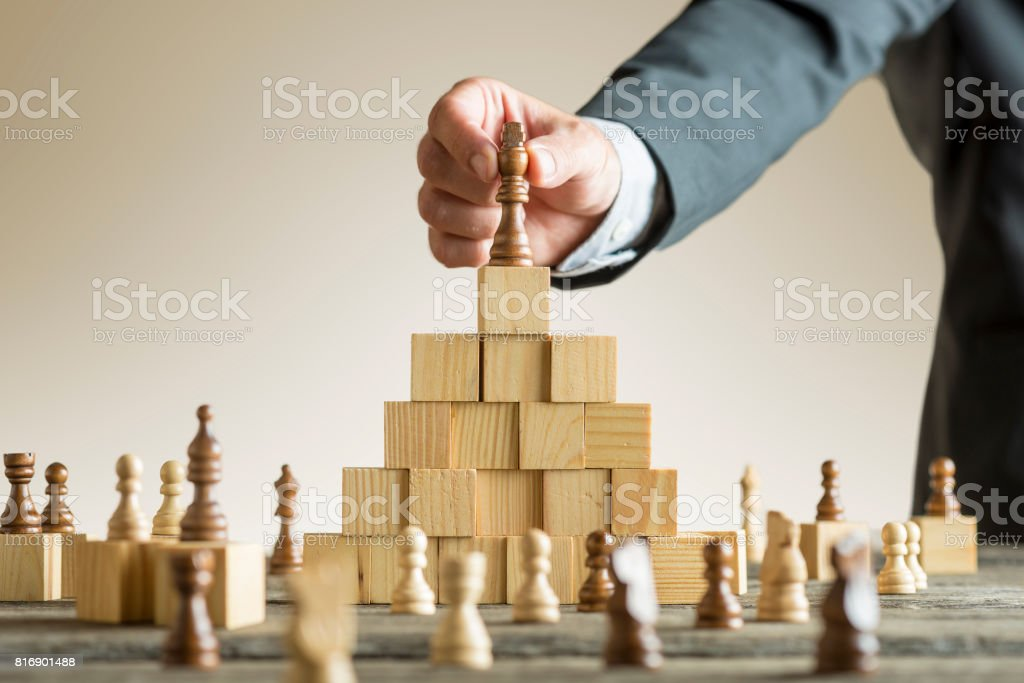 Businessman placing a chess piece on blocks stock photo