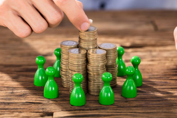 Businessman Placing Coins Over Stack With Green Figures stock photo