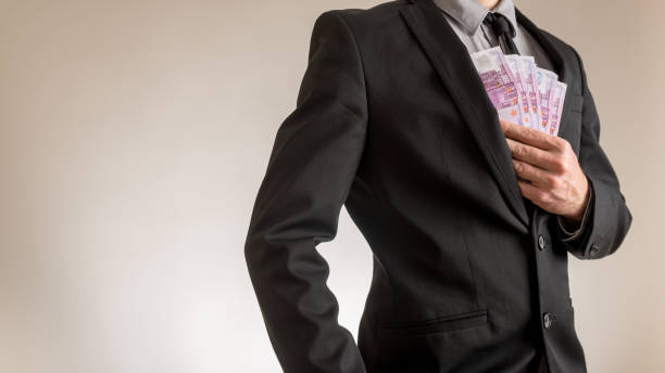 Businessman placing Euro bills in the inner pocket of his jacket stock photo