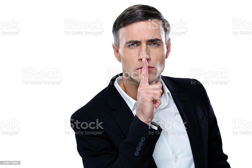 Businessman placing finger on lips saying shhh stock photo