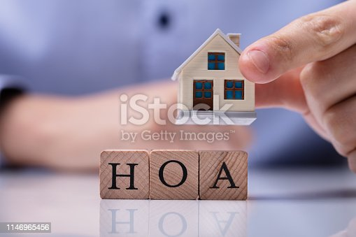 istock Businessman Placing House Models On HOA Cubic Blocks 1146965456
