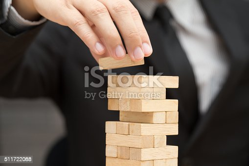 istock Businessman placing wooden block on a tower. Risk concept 511722088