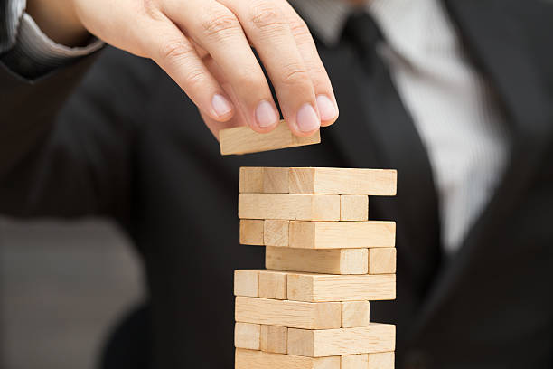 Businessman placing wooden block on a tower. Risk concept stock photo