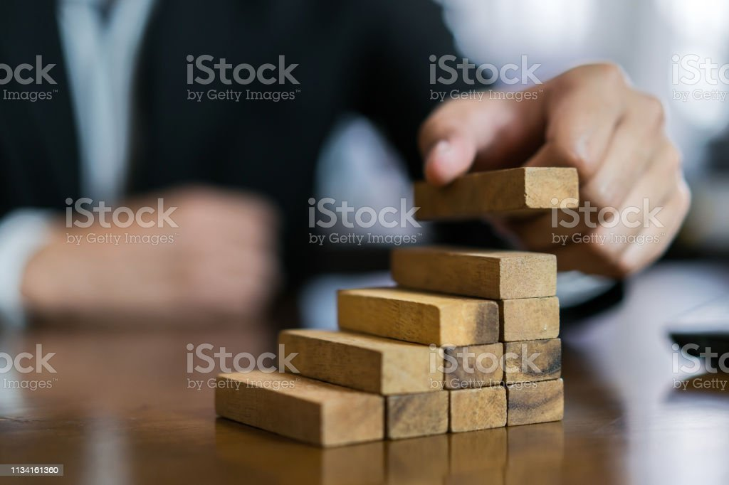 Businessman Planing And Strategy Putting Wooden Blocks Risk Or